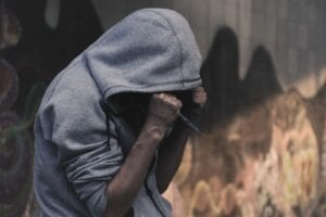 person with hoodie holding a syringe