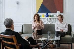 two women and a man talking in a room