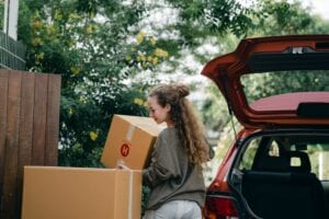 woman carrying box to new home