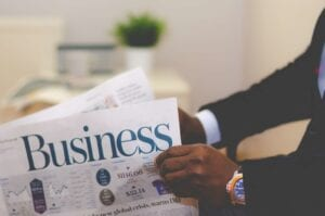 man holding white and blue business paper