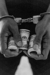 person holding a money while handcuffed